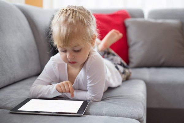 Young girl using tablet computer at home